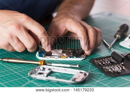 Man repairing broken smartphone, close up photo.