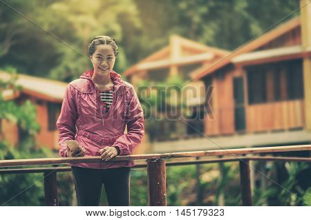 Vacation lifestyle scene of woman wearing sport cloths standing in resort. Woman activity on holiday in morning time concept with vintage filter effect