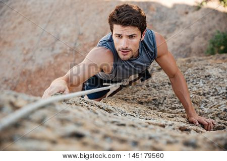 Man reaching for a grip while he rock climbs on a steep cliff
