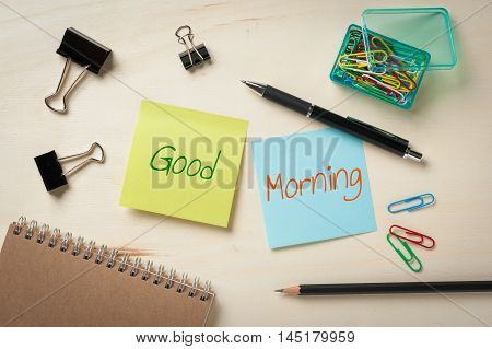 """Good morning"" is written on sticky paper including blue and green color with blank area for text or message stick on wood table with pen pencil paper clips and notebook in morning time"