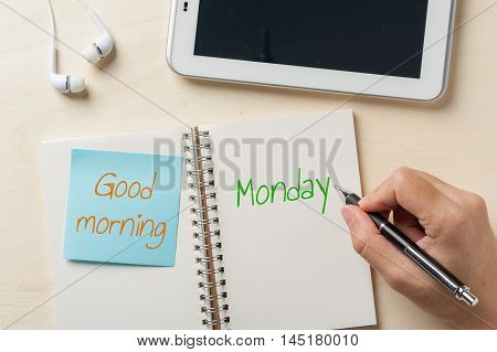 """""""Good morning monday"""" is written on notebook with sticky paper beside small tablet pc and in ear headset on wood table"""