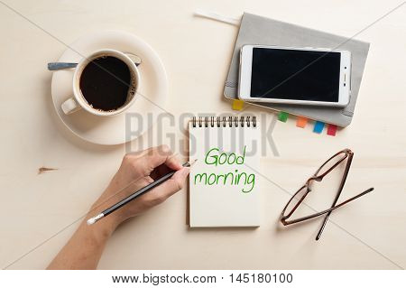 """Good morning"" is written on notebook on wood table with coffee cup smartphone and glasses beside in morning time"