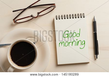 """""""Good morning"""" is written on opened notebook with blank area pen glasses and coffee cup on wood table in morning time"""