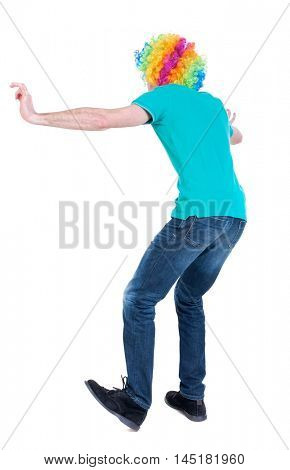 back view of dancing young beautiful man in clown wig. Curly man in a turquoise sweater and clown wig dancing.