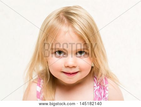Closeup portrait of beautiful blonde toddler baby girl with cheeky grin