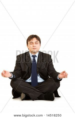 Meditating modern businessman sitting on floor isolated on white