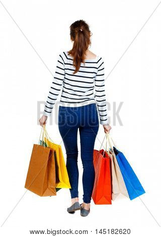 back view of going woman with shopping bags . beautiful girl in motion. Girl in a striped sweater went off shopping.