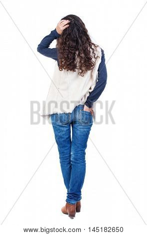 back view of standing young beautiful woman Long-haired girl with curly hair thoughtfully scratching his head.