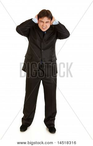 Annoyed businessman closing ears with hands isolated on white