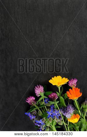 summer flowers over dark slate board background