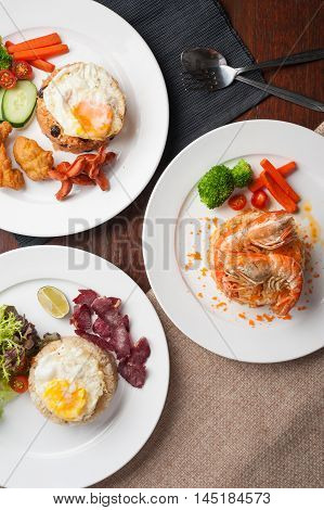 Top view of Thai modern cuisine set including shrimp fried rice fried rice with salted beef and raisin fried rice with sausage on wood table in restaurant