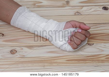 Gauze bandage the hand contusion. treating patients with hand with a wrist left male With  wrapping his injury On a wooden table