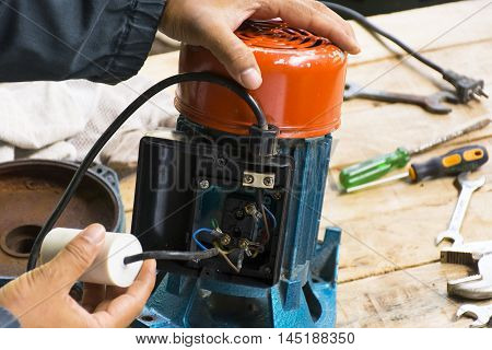 Electric motor  and man working equipment repair on cement floor background.Background motor or equipment.Zoom in 0001