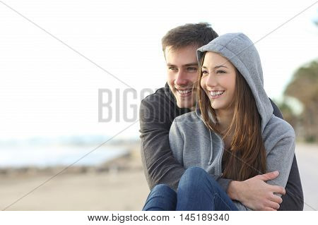 Casual happy teenager couple dating and hugging sitting outdoor and looking at horizon in the beach