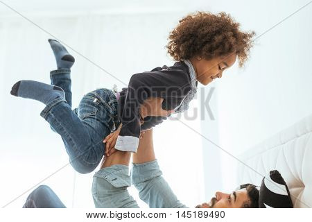African american girl having playful time with daddy.