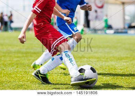 Boys kicking soccer ball. Footballer dribbling and kicking ball. Soccer players kicking ball on sports field. Competition game between youth football teams.