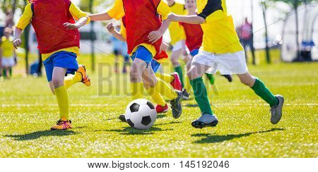 Kids kicking soccer ball on sports field. Youth european football teams playing soccer.