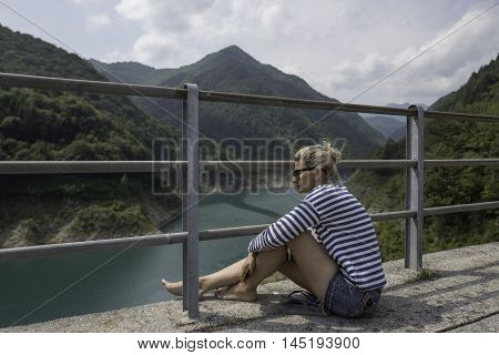 Beautiful girl is seating on the bridge and looking into the distance