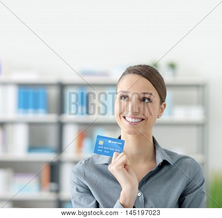 Young smiling woman at home holding a credit card and day dreaming about shopping