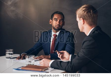 Two young businessmen in suits discussing documents together while sitting at a table in a modern boardroom