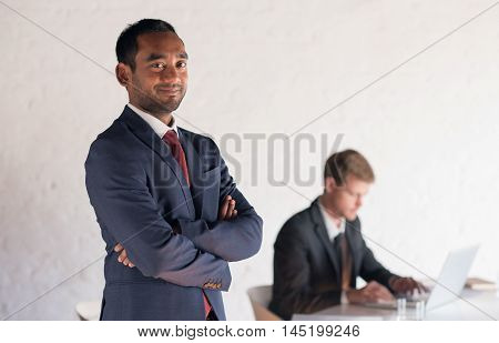 Portrait of confident and successful businessman standing in a modern boardroom with a colleague sitting in the background using a laptop
