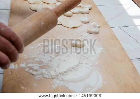 Dough Being Flattened On A Wooden Cutting Wooden Board
