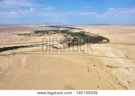Aerial view on the beautiful landscape of the Namib Desert and settlement in oasis. Flying on a small plane over the desert is one of the most popular tourist attractions in Namibia Africa