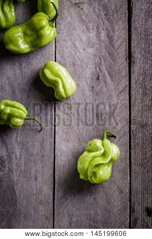 Hot habanero peppers on gray wooden background.