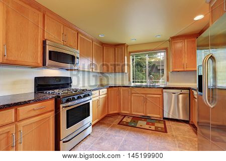 Maple Kitchen Cabinetry And Steel Appliances. Kitchen Interior.