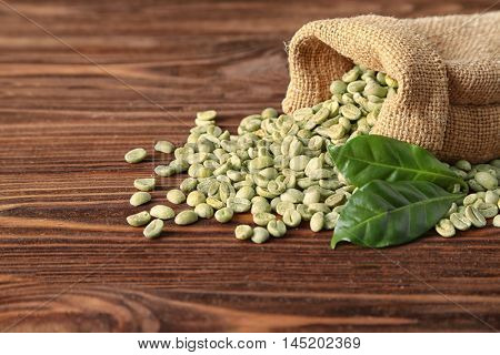 Coffee grains with green leaf in sackcloth on wooden table