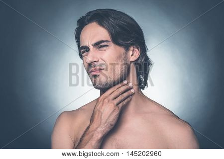 Feeling pain in throat. Portrait of young shirtless man expressing negativity while touching his neck and standing against grey background