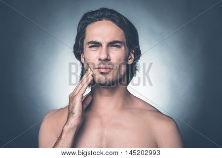 Feeling that awful toothache. Portrait of young shirtless man expressing negativity while touching cheek and standing against grey background