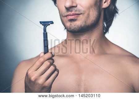 Time for new razor. Close-up young shirtless man holding razor and expressing negativity while standing against grey background
