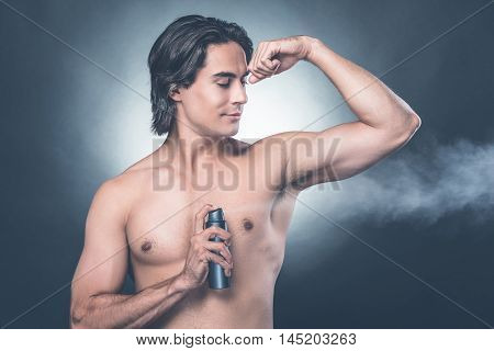 Getting fresh. Handsome young shirtless man spraying deodorant while standing against grey background