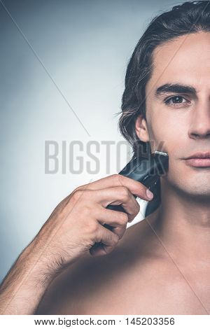 Shaving with electric razor. Half full of young shirtless man shaving with electric razor and looking at camera while standing against grey background