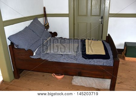 Old Salem North Carolina - April 21 2016: A simple wooden bed shared by the husband and wife at the colonial 1771 Miksch House