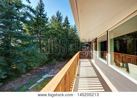 Long Empty Deck With Wooden Railings And Backyard View.