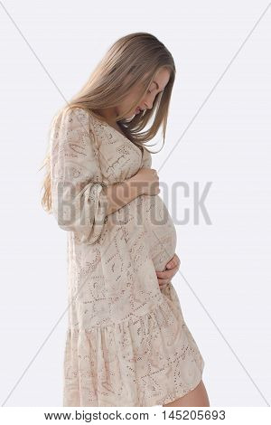 Silhouette pregnant woman looking at belly and strokes in a bright dress with long blond hair on white background