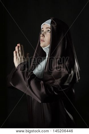Young catholic nun with pray. Photo on black background.