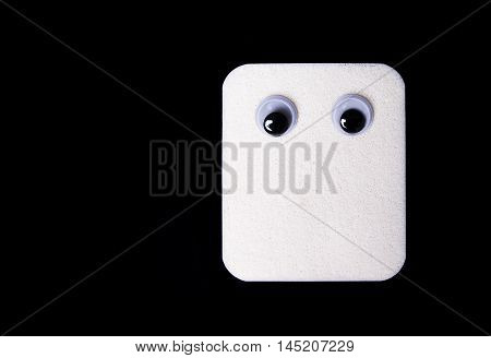 Make up - white sponge with googly eyes. isolated on black background.