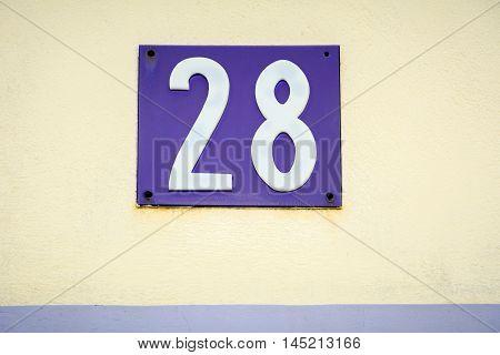 Purple enamel door number twenty eight on cream plaster wall in France