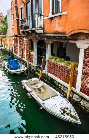 Canal with boats and colorful facades of old medieval houses in Venice Italy