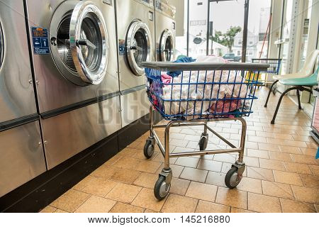 Industrial washing machines in a public laundromat with laundry in a basket