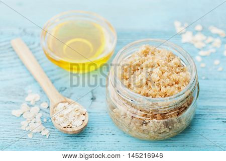 Body scrub of oatmeal sugar, honey and oil in glass jar on blue rustic table. Homemade cosmetic for peeling and spa care.