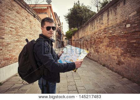 Young tourist man walking with a map at old city street
