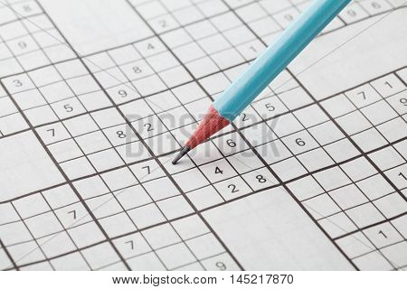 Crossword sudoku and blue pencil for entertainment, popular conundrum.