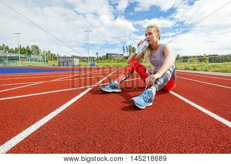 Full length of young woman drinking water from bottle and rests while sitting on running tracks