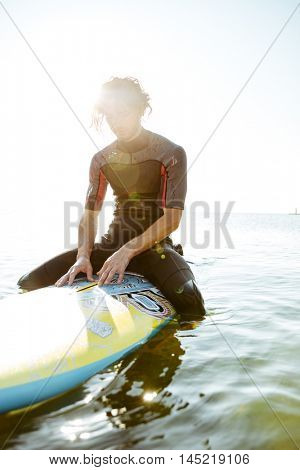 Smiling young surfer man in eyeglasses sitting on surf board in ocean and looking down