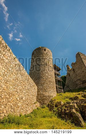 Vertical photo of very old medieval tower of damaged castle. Only ruins stayed to present. Few stones and rocks are in foreground with grass. Sky is dark blue with few clouds.