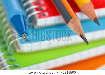 Closeup shot of pensil against defocused notebooks in background.Shallow dof. Focus on the tip of grey pencil.